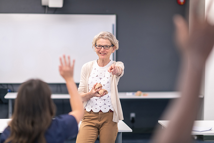 A professor in a classroom calling on a student raising their hand.