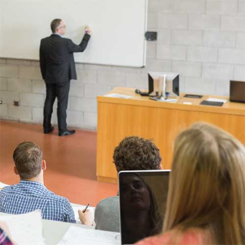 Picture of a lecture hall with instructor at whiteboard and students taking notes.