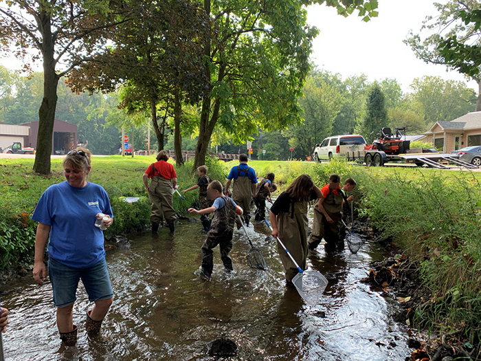 Da-Lite volunteers and students in waders are exploring a stream.