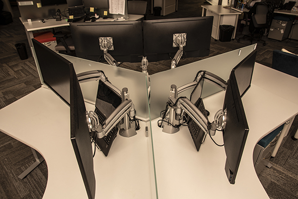 Monitor mounts around a desk shot from above.