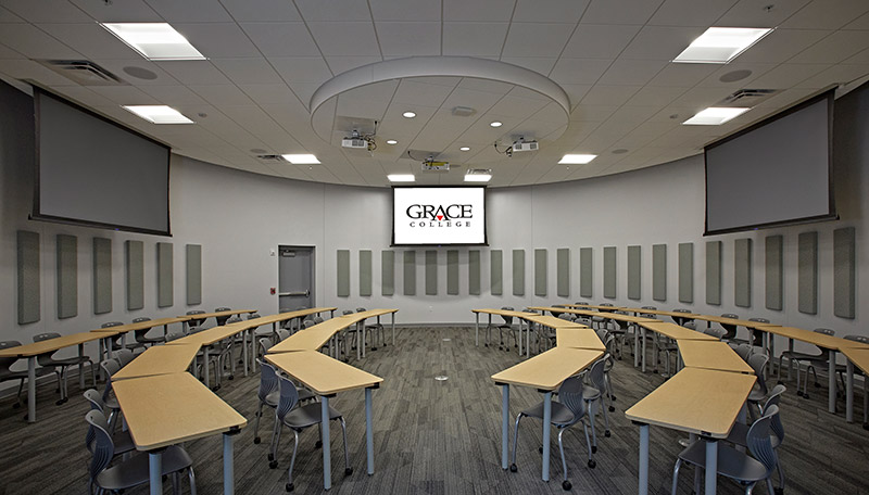 Classroom with rows of tables facing each other and projection screens at each end.