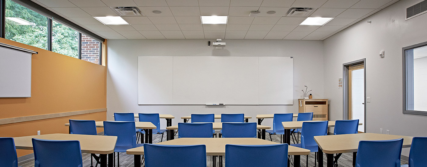Classroom with IDEA screen at the front and a projection screen on the side.