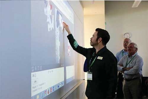 Attendees of the symposium use interactivity features of the IDEA Panoramic screens and Epson 595Wi short throw projectors to assemble puzzles