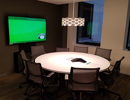 Conference room with round table and Tempo holding a display.