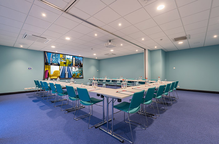 Small conference room with tables and projection screen.