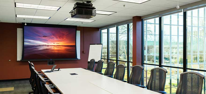 Conference room with a large table and chairs, projector screen and projector mount, in-wall PTZ camera and ceiling microphones.