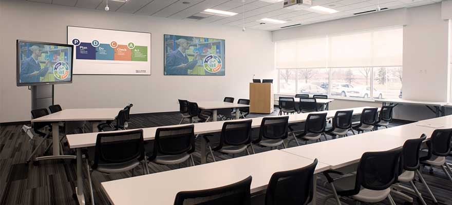 Large room with desks and chairs with a lectern, display cart, projector screens, projector mounts, camera tracking and ceiling microphones.
